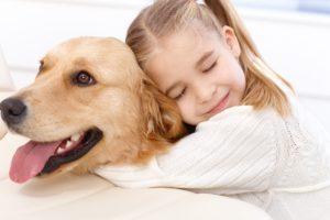 Copil strânge în brațe câinele familiei