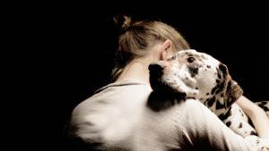 Stăpâna își îmbrățișează câinele