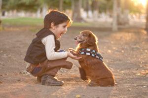 Băiețel ieșit la joacă alături de câinele său