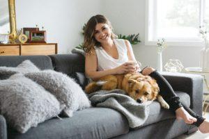 Câine levenește pe canapea alături de stăpână în casa acesteia